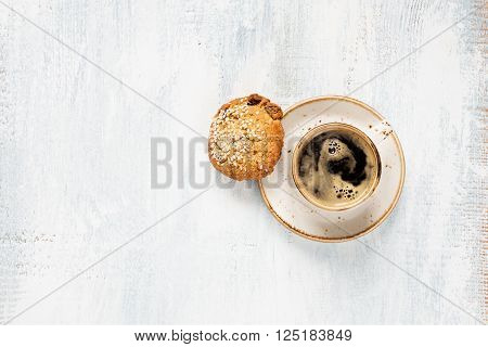 Black coffee with crema in vintage porcelain cup and oatmeal cookie on a light wooden background top view
