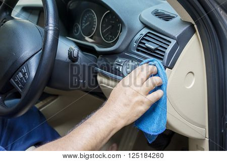 Close up of worker hand using a microfiber cloth to clean the car dashboard in the garage
