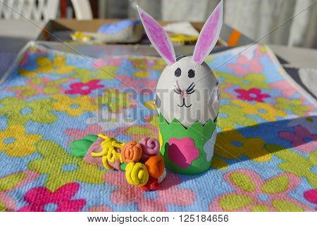 Easter bunny made of an egg shell with plasticine flowers on the flower background.