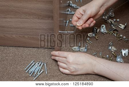 Small tools for assembly furniture, furniture brackets and fixing, closeup hand tighten the screw using the allen wrench.