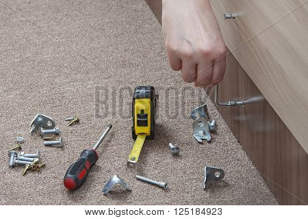 Key furniture screws,  close up carpenter hand  tightens screw with an allen wrench, screwing up of furniture screw.