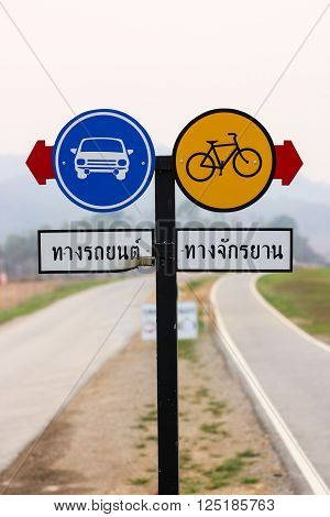 Pair of round traffic signboard with red arrow indicating: Car lane and Bicycle lane