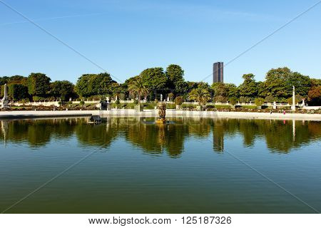 Color DSLR stock image of pond in Luxembourg Gardens with the Montparnesse Tower in the background.The Paris, France park is popular with residents and tourists. Horizontal with copy space for text