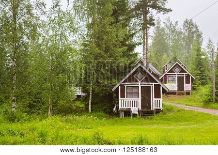Summer outdoor recreation, Scandinavian vacation. Small wooden camping houses under the summer rain on a green meadow in campsite among trees. Palvaanjarven Campsite, Luumaki, Lappeenranta, Finland, Suomi