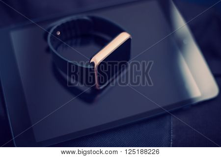 Smart Wrist Watch Laying On A Tablet Pc