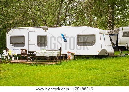 LAPPEENRANTA, FINLAND - JUNE 13, 2014: Summer outdoor recreation, Scandinavian vacation in house on wheels. Camping van parked on a green meadow in campsite among trees. Palvaanjarven Campsite, Luumaki, Lappeenranta, Finland, Suomi
