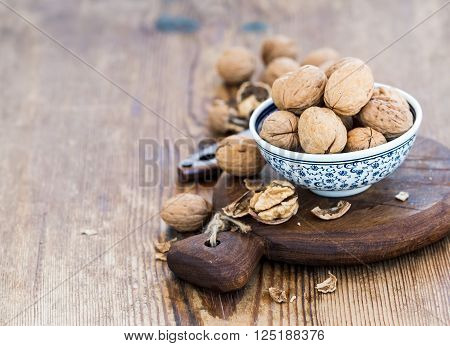 Walnuts in ceramic bowl and on wooden board with nutcracker over  rustic wooden background, selective focus