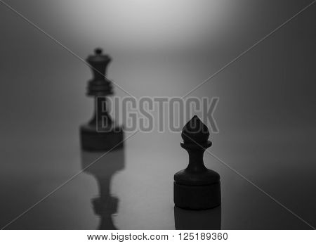Rows of black chess figures and a single white pawn on the chessboard (isolated on white, selective focus on the white pawn)