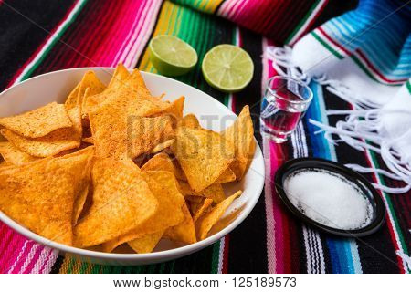 Nachos chips in a bowl tequila lime and salt over a colored poncho