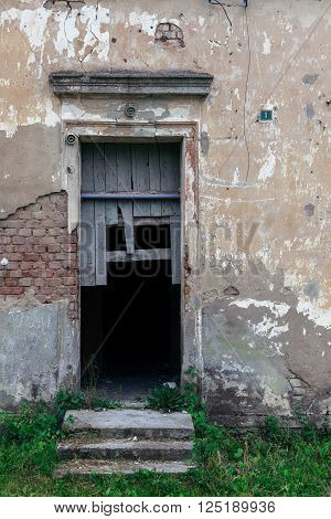 Decayed entrance with broken doors to an abandoned building