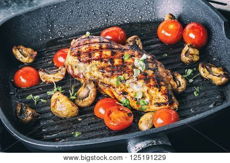 Grilled chicken breast in different variations with cherry tomatoes mushrooms herbs cut lemon on a wooden board or grill pan. Traditional cuisine. Grill kitchen