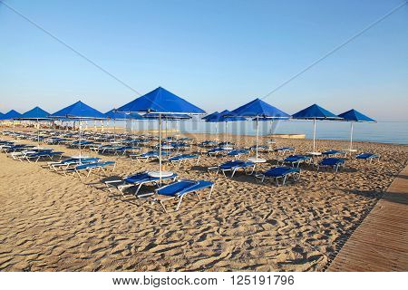 Blue umbrellas and chaise longue on empty sandy beach in the morning, Crete, Greece
