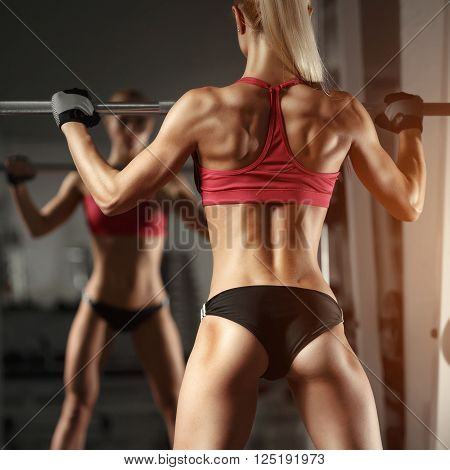 Beautiful fitness sexy woman doing squat workout in gym. Fitness, sport, powerlifting and people concept
