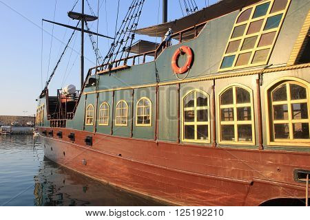 replica of the medieval pirate warship is used for tourist trips along the coast of Crete, Greece. Sunset light