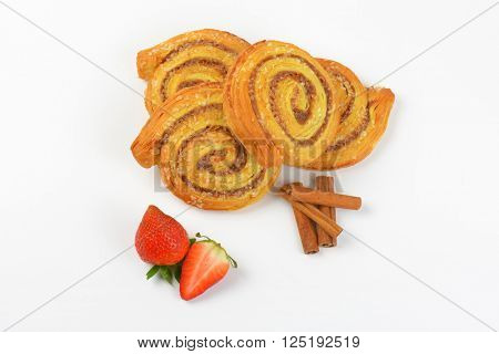 sweet cinnamon rolls, cinnamon sticks and strawberries on white background
