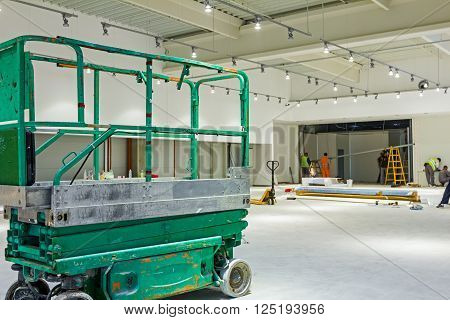 Scissor lift platform is inside of new big hall in building process.