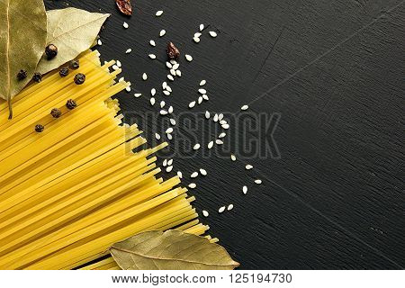 Raw spaghetti and Bay leaf, barberry, pepper, sesame seeds on black wooden background, top view place for text