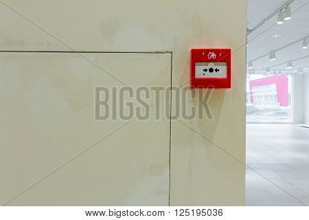 Red fire alarm panel box is on the wall to smash glass and press button. Every building is required to have a fire alarm.