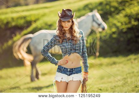 Young Cowgirl and Horse Outdoors. Sexy Fashion Model