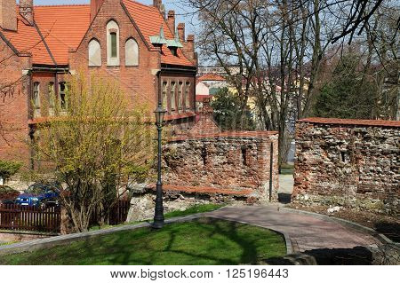 Wieliczka, Poland - April 04, 2016: Saltworks Castle. Fragment of the defensive walls of the fifteenth century. On the left Wieliczka district Office.