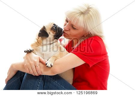 A woamn in a red shirt kissing a pug