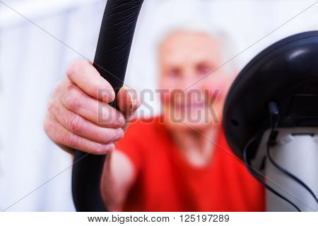 Close-up of an elderly woman's hands doing sport, training on a stationary bicycle indoors in the nursing home.