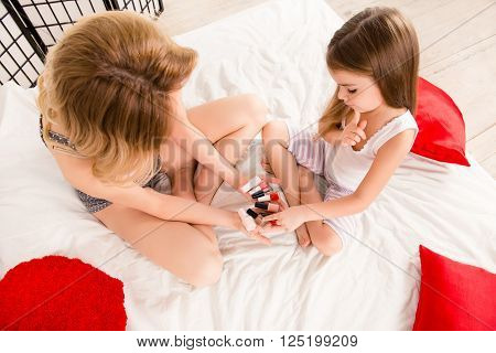 Top View Portrait Of  Mother And Daughter Choosing Color Of Varnish