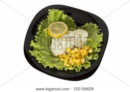 Fish dish on a black plate with greens onion lemon and corn. Isolation on a white background. Clipping path.