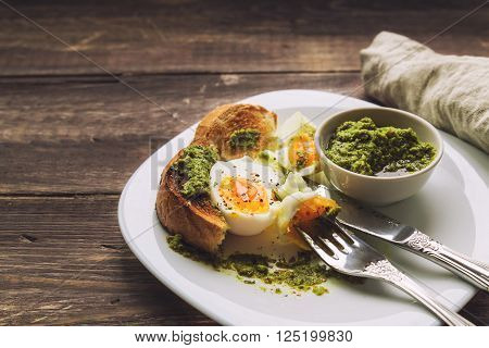 Boiled egg with toasted bread and pesto sauce on rustic wooden background. Selective focus.
