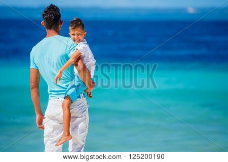 Father and son playing on the tropical white beach at the day time. Concept of friendly family.