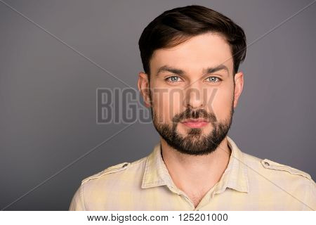 Portrait Of Minded Strict Handsome  Brunet With Beard On Gray Background