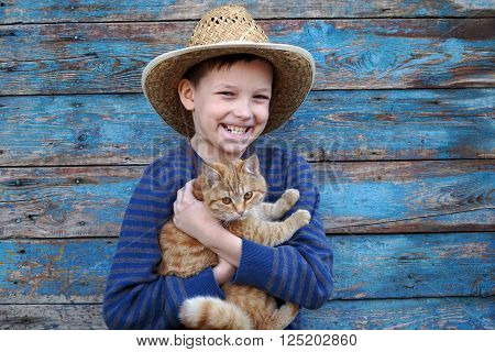 boy playing with a auburn cat outdoors