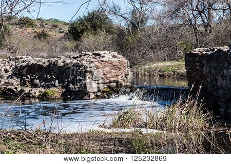 The Old Mission Dam with waterfall and forest background at Mission Trails Regional Park in San Diego, California.