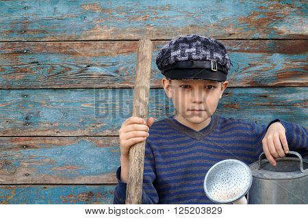 boy with a shovel and a watering can is sitting near wooden wall