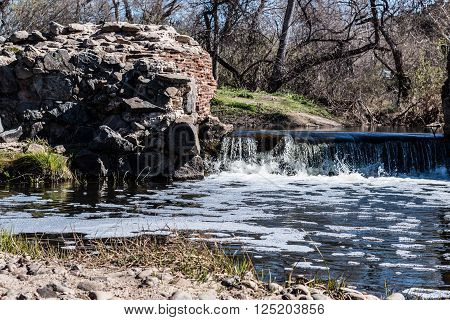 Waterfall and surrounding forest landscape of Old Mission Dam at Mission Trails Regional Park in San Diego, California.