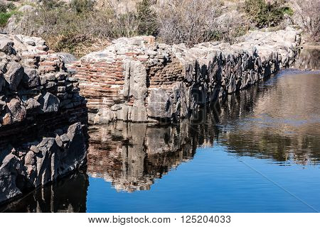 Rear view of stone walls of historic Old Mission Dam at Mission Trails Regional Park in San Diego, California.