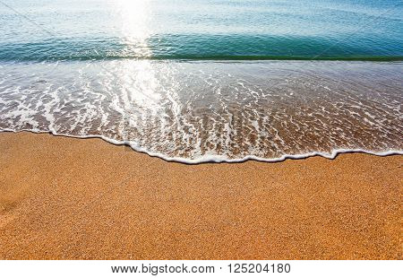Sun light reflected on soft wave of the sea on the sandy beach