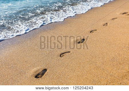 Sea wave and foot marks on the sandy beach