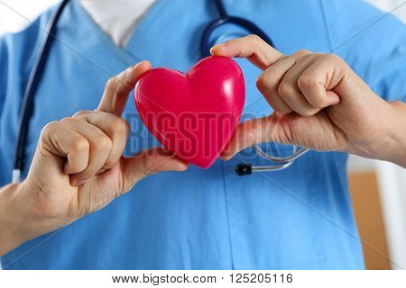 Male Medicine Doctor Wearing Blue Uniform Hold In Hands Red Toy Heart