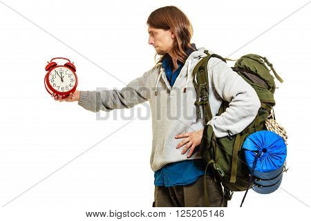 Travel time season. Young man backpacker holding clock. Hiker on vacation summer trip journey. Last minute holidays. Isolated on white background.