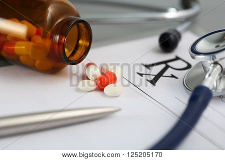 Prescription lying on table with stethoscope, pen and pile of pills fell out from jar. Panacea and patient life save, prescribing treatment, legal drug store concept. Medical form ready to be used