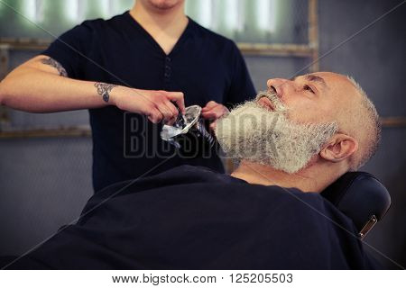 Barber shaving with brush shaving foam an senior man in a barber's shop