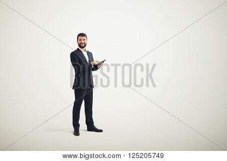 A smiling businessman in a formal wear with black phone in his hands