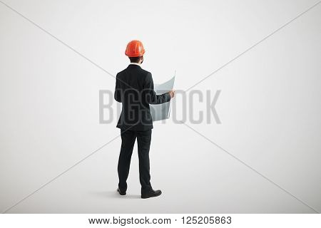 Back view of standing man in formal wear and in a hard hat holding blueprints