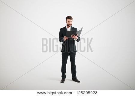 Man in formal wear and white shirt familiarize with the materials in the folder