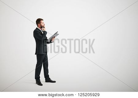 Serious man in a formal wear touching his beard and looking forward