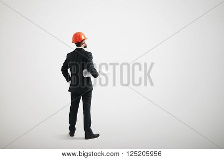 Back view of standing man in a formal wear and in a hard hat holding blueprints