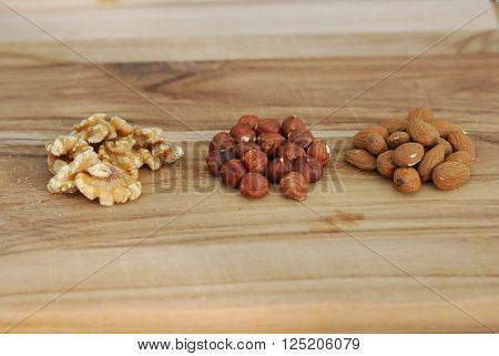 Three types of nuts on a wooden breadboard