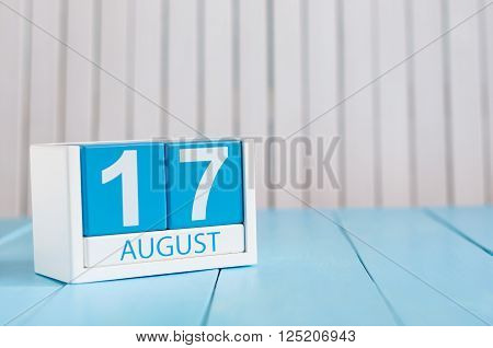 August 17th. Image of august 17 wooden color calendar on blue background. Summer day. Empty space for text.