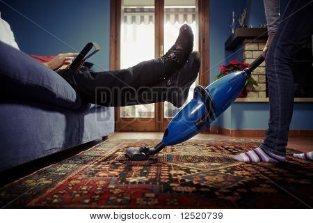 Man Relaxing While Woman Doing Chores At Home